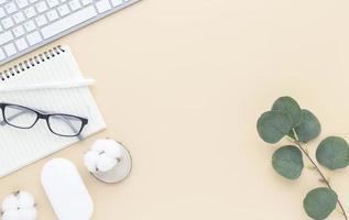 Vista superior de la mesa de escritorio de oficina con suministros de oficina, mesa beige, foto