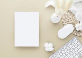 vista superior de la mesa de escritorio de oficina. jarrón de cerámica con junco y algodón foto