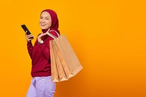 Cheerful asian woman holding smartphone and showing shopping bags photo