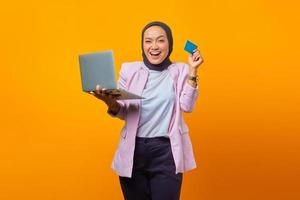 Cheerful asian woman holding laptop and showing credit card photo