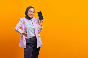 Cheerful asian woman showing smartphoneover yellow background photo