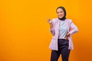 Cheerful attractive asian woman pointing finger at empty space photo