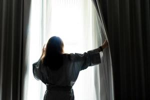 Beautiful woman is opening the curtain at the window in the morning photo
