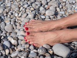 Pies femeninos en el fondo de la playa de guijarros, relajación de verano foto