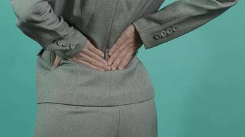 dolor de espalda. mujer de negocios con lesión en la espalda. video