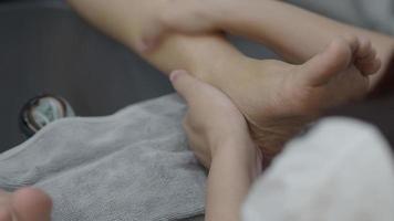 Foot care. Woman bare feet massaging and nail cail at spa shop. video