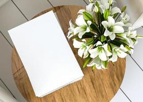 papel blanco colocado sobre una mesa de madera con un jarrón de flores. foto