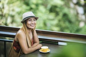 Happy young woman with latte coffee in morning photo