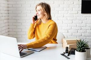Young woman in yellow sweater using laptop and calling on the phone photo