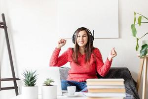 woman in red sweater and black headphones sitting on the couch dancing photo