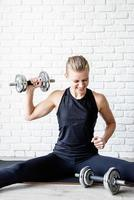 Young athletic woman working out with dumbbells photo