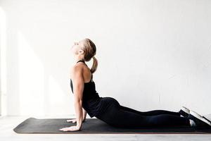 young blond woman doing yoga or stretching at home photo