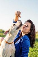 Atractiva mujer joven alimentando a su perro en el parque foto