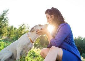 Atractiva mujer joven abrazando a su perro en el parque en la puesta de sol foto