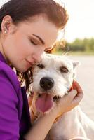 young attractive woman hugging her dog in the park photo