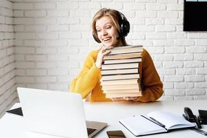 Mujer en auriculares negros estudiando en línea sosteniendo una pila de libros foto