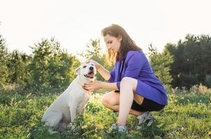 young attractive woman hugging her dog in the park in the sunset photo