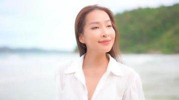 Asian woman enjoys a day at the beach video