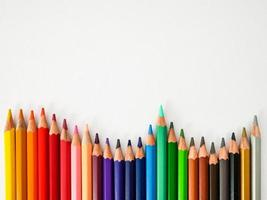 Fila de lápices de colores transparente sobre fondo de papel de pintura blanca foto