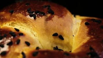 Black cumin seeds are falling on a yummy bun in slow motion video