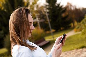 Woman using mobile smart phone in the park photo