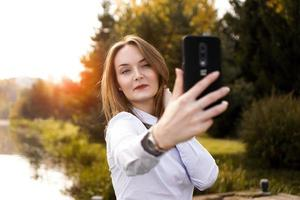 Portrait of cheerful young woman making selfie photo