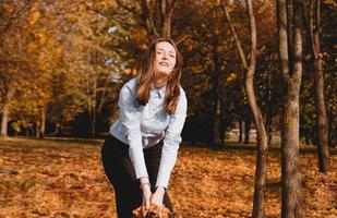 Woman throwing yellow leaves in the air photo