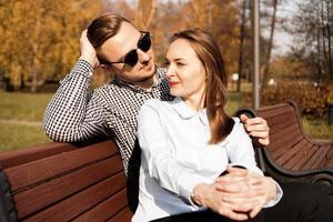 Feliz pareja sonriente en un banco del parque en otoño foto