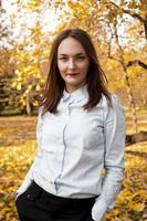 Portrait of beautiful young woman in autumn park photo