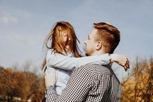 Cute couple having fun in autumn park - selective focus photo