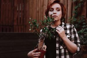 Woman with short red hair in plaid shirt holding a flower in pot photo