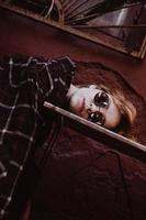 Woman with short red hair in sunglasses, head lies on table photo