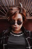 Portrait of attractive cheeky woman with short red hair in sunglasses photo