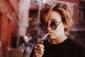 Girl with short red hair and mirror sunglasses smoking cigarette photo