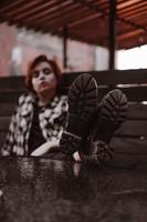Young woman with short red hair in a bar put her legs on table photo