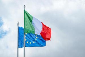 Italian and European Union flags waving against a cloudy sky photo
