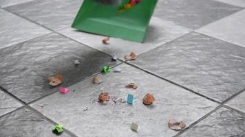 barre los trozos de papel y el polvo de los pisos de baldosas con una escoba. video