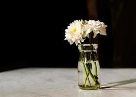 Ramo de flores blancas en un jarrón sobre la mesa de madera foto