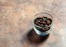 Granos de café frescos en un tazón de vidrio sobre un fondo foto
