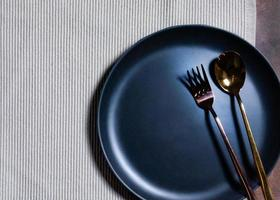 Empty plate with spoon and fork on Napery background, table setting photo