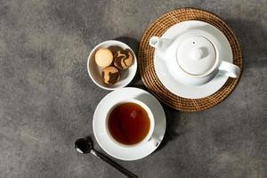 Taza de té de porcelana blanca y tetera, té inglés en la mesa foto