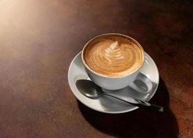 Cup of hot latte art in afternoon light on wooden table photo
