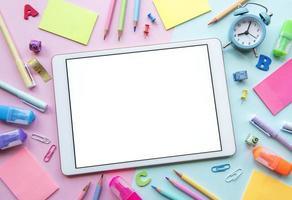 Bastidor de diferentes artículos de papelería sobre fondo rosa y azul. foto