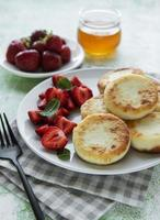 Cottage cheese pancakes, ricotta fritters on ceramic plate photo