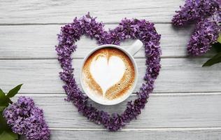 Lilac flowers and cup of coffee photo