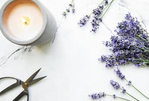 flores de lavanda, vela y tijeras foto