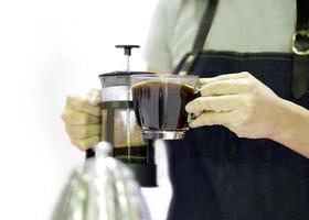 Barista pours coffee from a french press in the cup photo