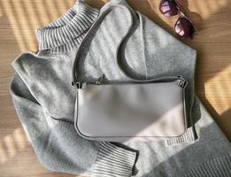 pequeño bolso de piel beige y jersey de mujer gris foto