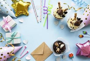 A top down view of common birthday party items in a border frame. photo
