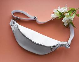 Bolso de cuero con cinturón blanco y flores sobre un fondo naranja claro foto